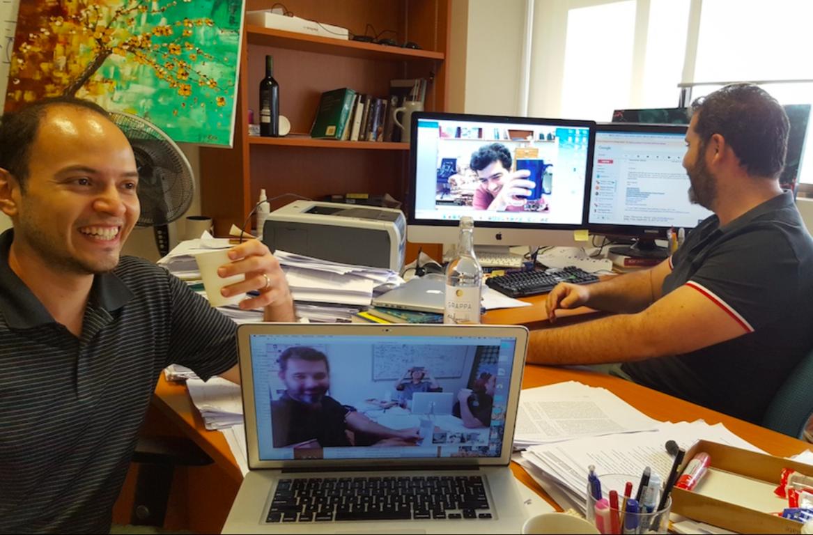 ทิว-จิรวัฒน์ ตั้งปณิธานนท์ (คนถือกล้องในจอคอมพิวเตอร์ด้านล่าง) กับเพื่อนๆ ทีมวิจัยชิปคอมพิวเตอร์ควอนตัมที่กูเกิ้ล สิงคโปร์